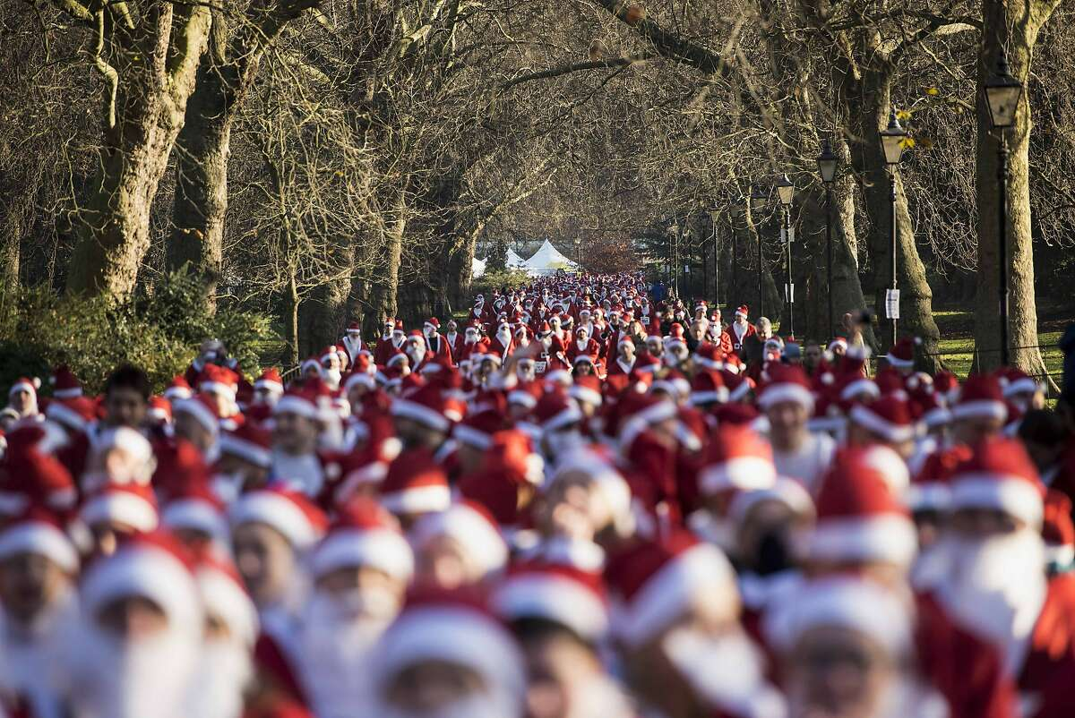 TOPSHOTS Charity runners dressed as Father Christmas await the start of the 'Santa Run' charity fun run in Battersea Park in London on December 6, 2014. Hundreds of participants dressed in Santa suits and white beards ran through Battersea park in aid of winter sports charity Disability Snowsport in this 6km festive fun run. AFP PHOTO / NIKLAS HALLE'NNIKLAS HALLE'N/AFP/Getty Images