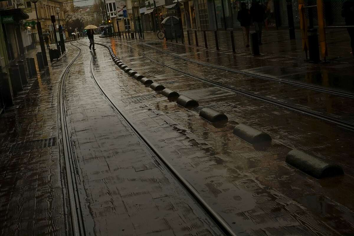 A pedestrian shelters from the rain with an umbrella as he passes tram tracks, in Vitoria, northern Spain, Saturday, Dec. 6, 2014. (AP Photo/Alvaro Barrientos)