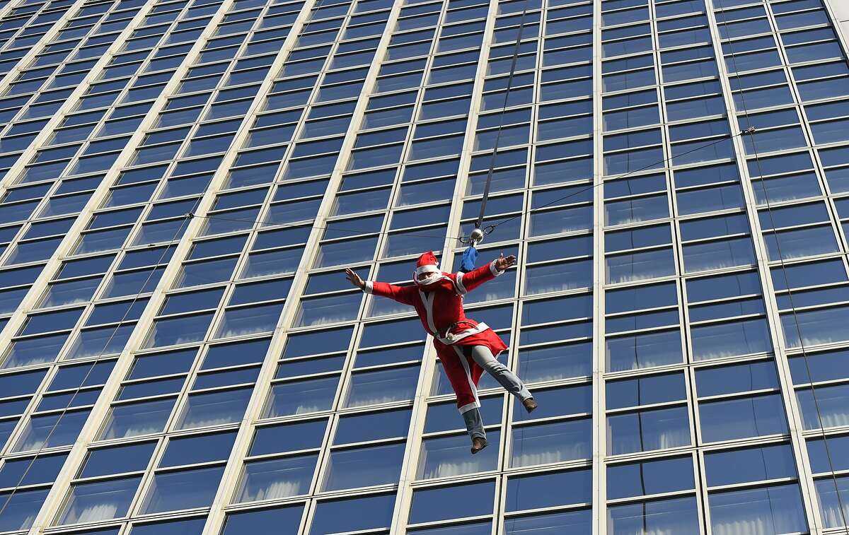 NO, DON'T DO IT, SANTA! St. Nicholas plunges from the top of the Forum hotel in Berlin's district. Fortunately, he had a parachute strapped to his back.