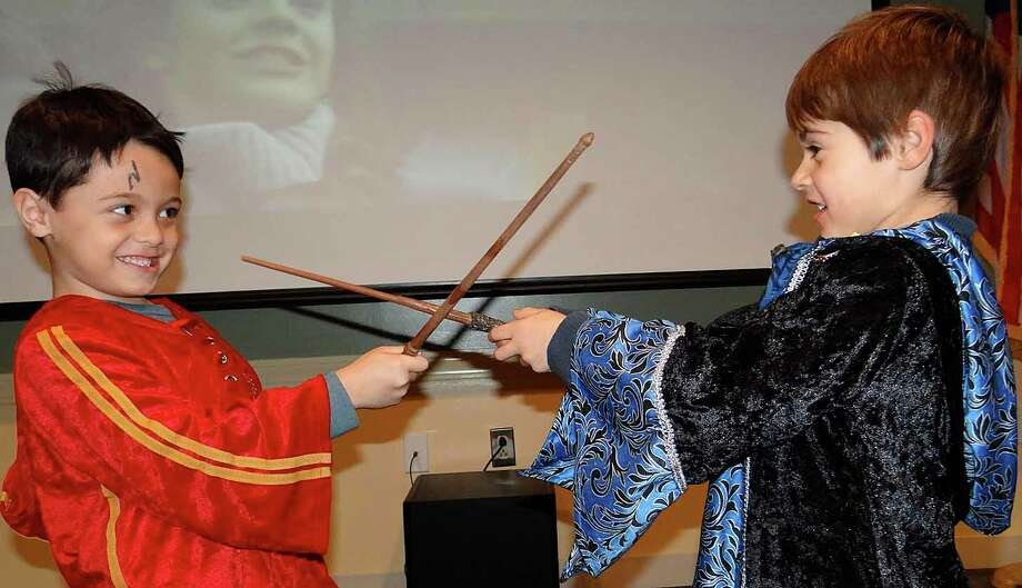 Young wizards Connor Sicat, 5, and Morgan Kofron, 5, duel at the Hogwarts Yule Ball at the Fairfield Public Library. Photo: Mike Lauterborn / Fairfield Citizen