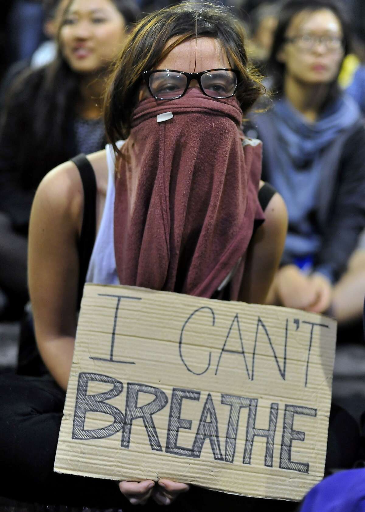 A girl who declined to give her name holds a sign in front of a police skirmish line during demonstrations in Berkeley, California on Saturday, December 6, 2014. Protesting continued through the night in response to the grand jury verdicts in the shooting death of Michael Brown in Ferguson, Missouri and the chokehold death of Eric Garner in New York City.