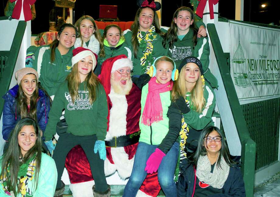 Making a stop to say 'hi' to Santa Claus during the Greater New Milford Chamber of Commerce's traditional Festival of Lights are the New Milford Bulls' Junior Midget Pop Warner cheerleaders, from left to right, front, Mariana Miranda and Alexandra Mann; Santa's row, Olivia Meyer, Madisyn Martinelli, Santa Claus, Olivia Sarko and Valerie Martarella; and, back row, Ariana Espinal, Sydney Crookshank, Julia Colley, Mykenzee Baier and Megan Gebert. The girls will perform Dec. 11 on ESPN 3 as part of thh Pop Warner national cheerleading championships. Nov. 29, 2014 Photo: Trish Haldin / The News-Times Freelance