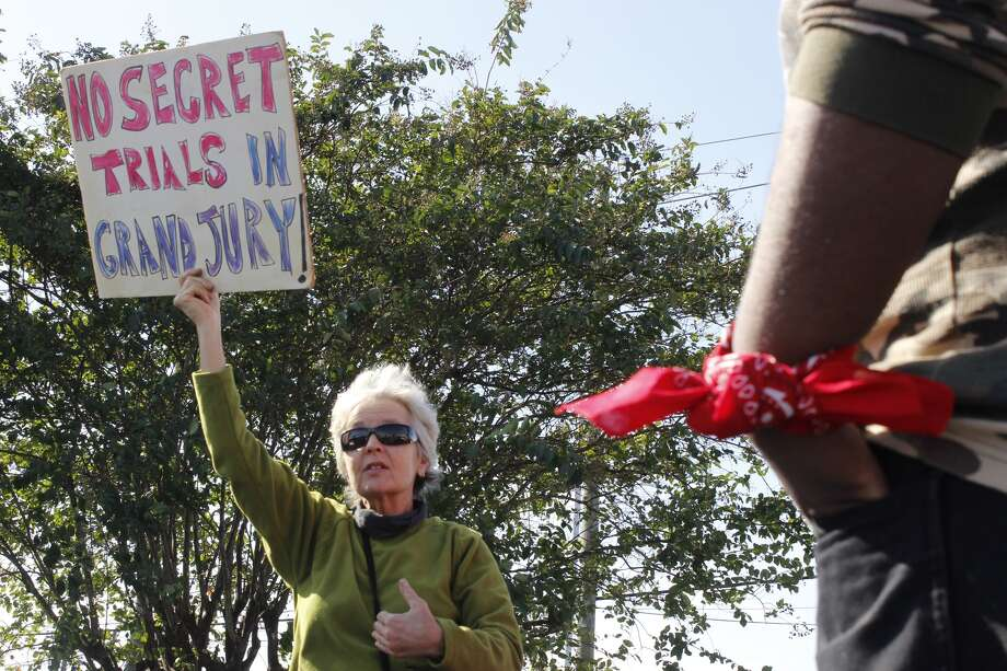 Maggi Carter holds up a sign before the group begins the Sunday march in solidarity with all victims of police brutality.