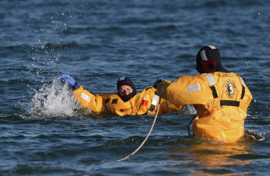 """Marine Officer Dave Stewart, left, plays the victim as fellow Marine Officer Joe Turcsyni """"rescues"""" him during a cold water rescue demonstration at Greenwich Point Park in Old Greenwich, Conn. Sunday, Dec. 7, 2014.  Greenwich Marine Officers explained to a small group cold water rescue strategy and challenges while doing a live demonstration in the water of the Long Island Sound and letting kids practice with rescue devices. Photo: Tyler Sizemore / Greenwich Time"""