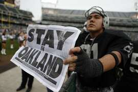 "Oakland Raiders' fan Art Padilla, III holds a ""Stay in Oakland"" sign before Raiders play the San Francisco 49ers in NFL game at O.co Coliseum in Oakland, Calif., on Sunday, December 7, 2014."