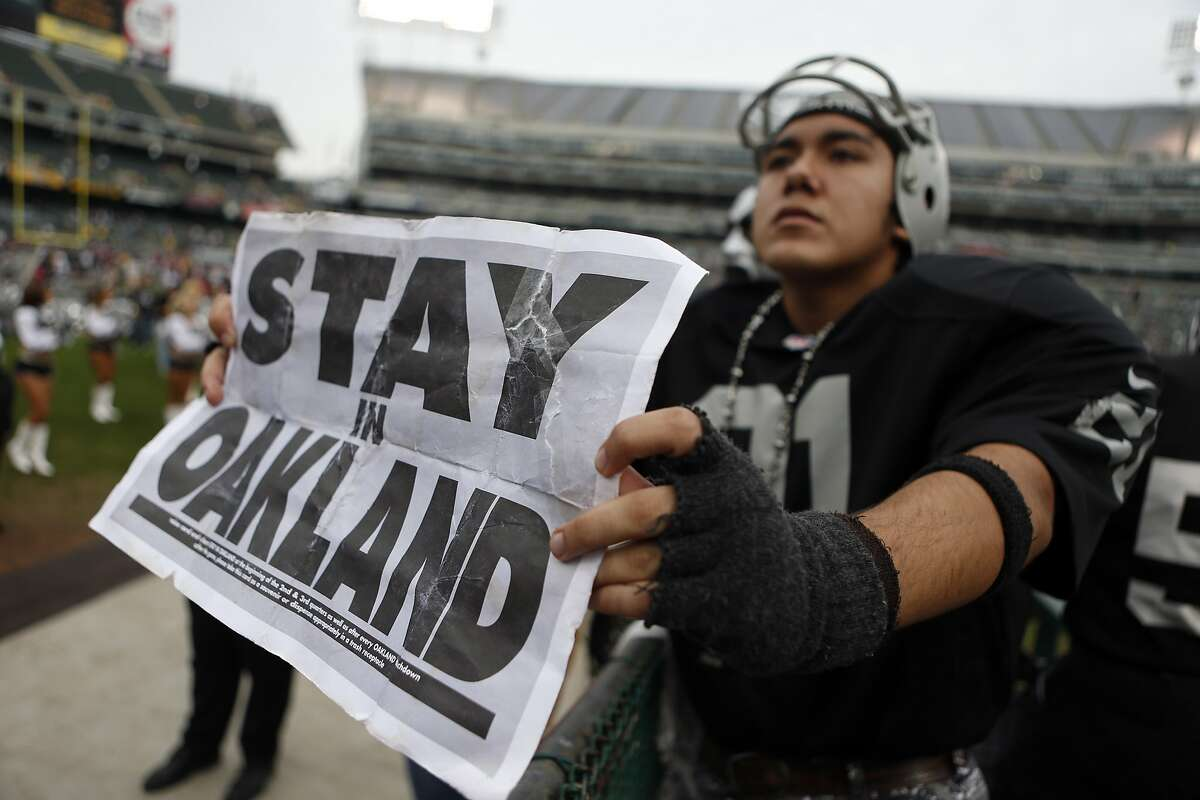 """Oakland Raiders' fan Art Padilla, III holds a """"Stay in Oakland"""" sign before Raiders play the San Francisco 49ers in NFL game at O.co Coliseum in Oakland, Calif., on Sunday, December 7, 2014."""