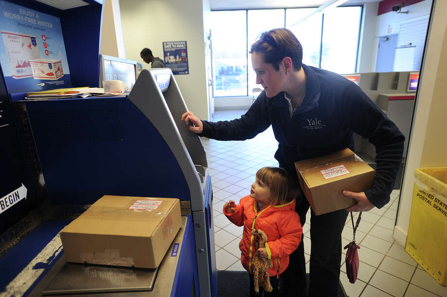 With daughter Charlie, 2, in tow, Amy Ahasic, of Fairfield, mails out Christmas presents at the Fairfield Post Office at 357 Commerce Drive in Fairfield, Conn. on Sunday, December 7, 2014. Several area post offices are now open from 1-5 pm on Sundays to help with the added mailing volume during the holiday season. Photo: Brian A. Pounds / Connecticut Post