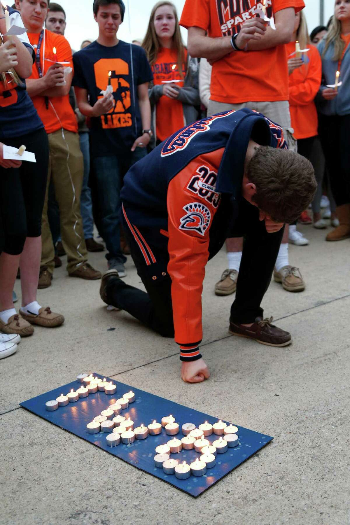 Shane Postma reacts during a candle light vigil for Seven Lakes student Trent Weber, Sunday, Dec. 7, 2014, in Houston. Trent Weber, a 17-year-old senior at Seven Lakes, and Terra Kubala, a 16-year-old sophomore at Cinco Ranch, were killed early Sunday morning after a pick-up truck flipped over in Katy.