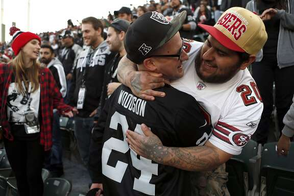 Oakland Raiders' fan Jason Fordyce and San Francisco 49ers' fan Nick Raynor embrace in final minutes of Raiders' 24-13 win in NFL game at O.co Coliseum in Oakland, Calif., on Sunday, December 7, 2014.
