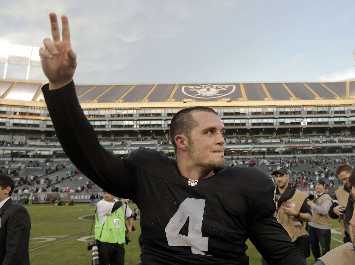 Derek Carr (4) waves to the crowd after defeating the 49ers 24-13 at O.co Coliseum in Oakland, Calif., on Sunday December 7, 2014.