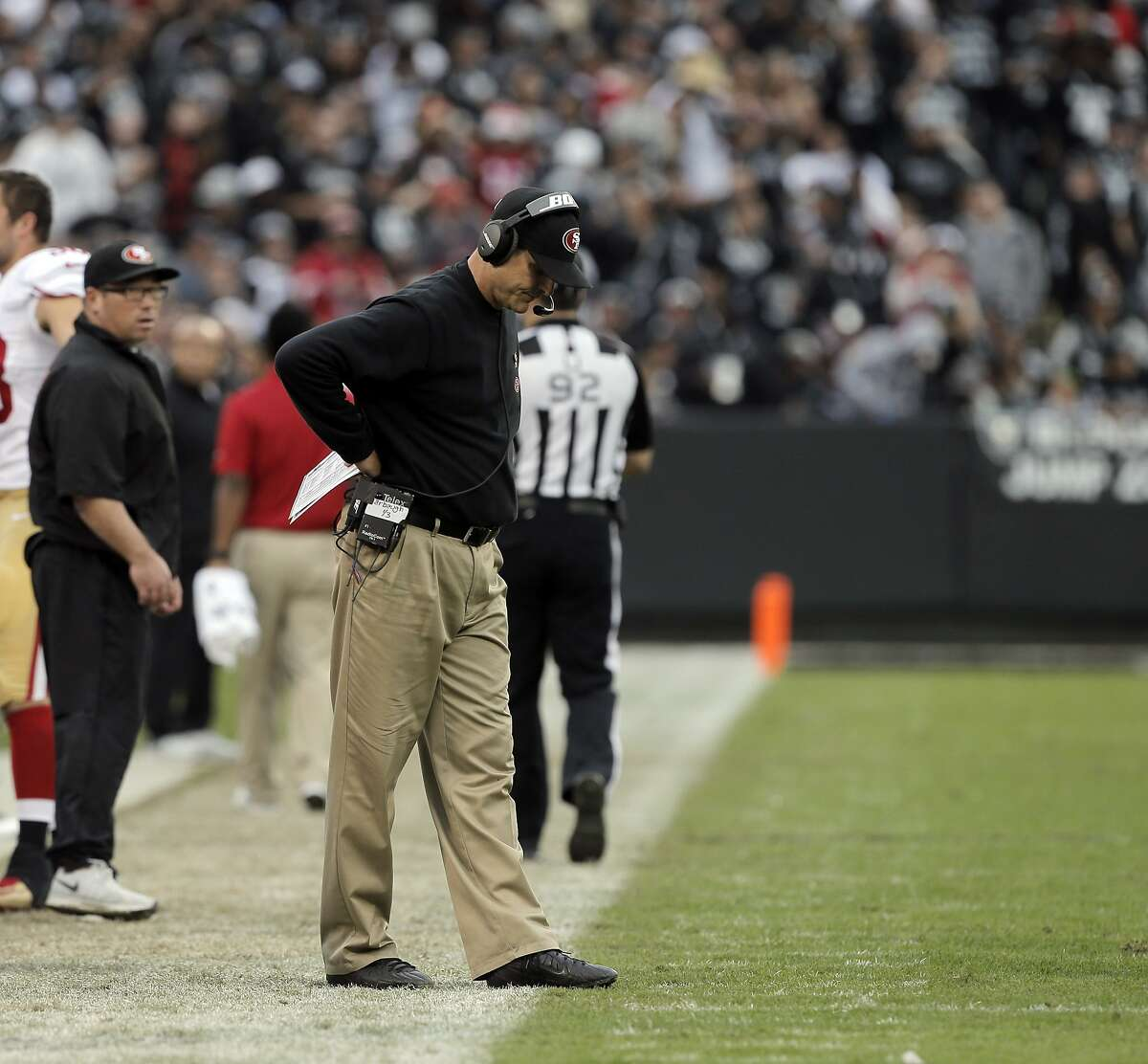 Jim Harbaugh walks along the sidelines during the second half of the Raiders game against the 49ers at O.co Coliseum in Oakland, Calif., on Sunday December 7, 2014.