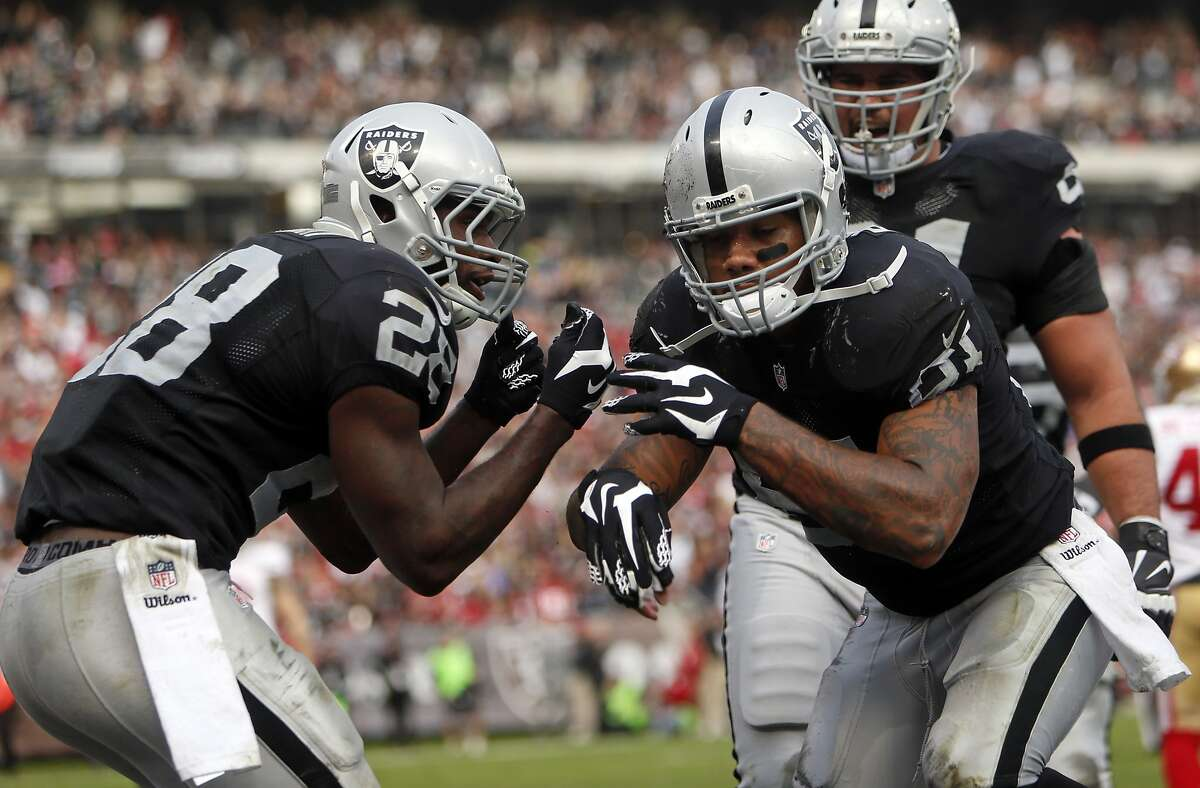 Oakland Raiders' Mychal Rivera celebrates his 4th quarter touchdown reception with Latavius Murray during 24-13 win over San Francisco 49ers in NFL game at O.co Coliseum in Oakland, Calif., on Sunday, December 7, 2014.