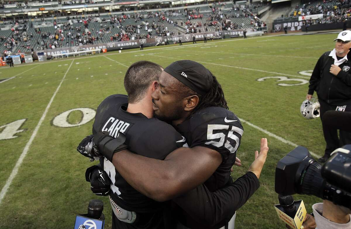 Derek Carr (4) hugs Sio Moore (55) after the Raiders game against the 49ers at O.co Coliseum in Oakland, Calif., on Sunday December 7, 2014. The Raiders defeated the 49ers 24-13.