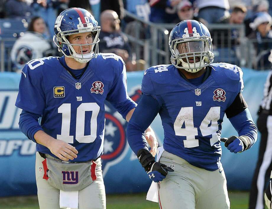 New York Giants quarterback Eli Manning (10) congratulates running back Andre Williams (44) after Williams scored a touchdown on a 50-yard run against the Tennessee Titans in the second half of an NFL football game Sunday, Dec. 7, 2014, in Nashville, Tenn. (AP Photo/Mark Zaleski) ORG XMIT: TNMH123 Photo: Mark Zaleski / FR170793 AP