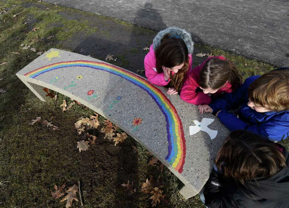 """Blue Creek Elementary School students, Julia Repko, left, Marisa Mullen, Kyle Hume and Hannah Bouchard, right, gather around the """"buddy bench"""" Tuesday afternoon, Dec. 2, 2014, at Blue Creek Elementary School in Latham, N.Y. The """"buddy bench"""" is a safe harbor where students can sit to indicate to others that they are feeling left out or bullied. Other children can then go sit with them or invite them to join in play, or teachers can ask what's wrong. (Skip Dickstein/Times Union) Photo: SKIP DICKSTEIN / 00029532A"""