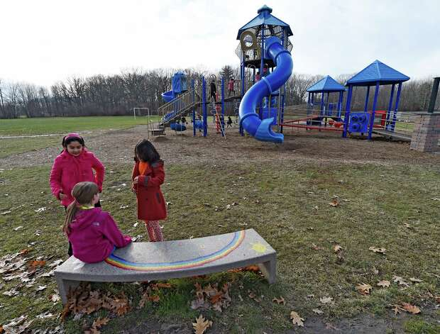 """Blue Creek Elementary School students, Aliza Zehra, left, Julia Repko, seated, and Zainab Bibi, right, gather around the """"buddy bench"""" Tuesday afternoon, Dec. 2, 2014, at Blue Creek Elementary School in Latham, N.Y. The """"buddy bench"""" is a safe harbor where students can sit to indicate to others that they are feeling left out or bullied. Other children can then go sit with them or invite them to join in play, or teachers can ask what's wrong. (Skip Dickstein/Times Union) Photo: SKIP DICKSTEIN / 00029532A"""