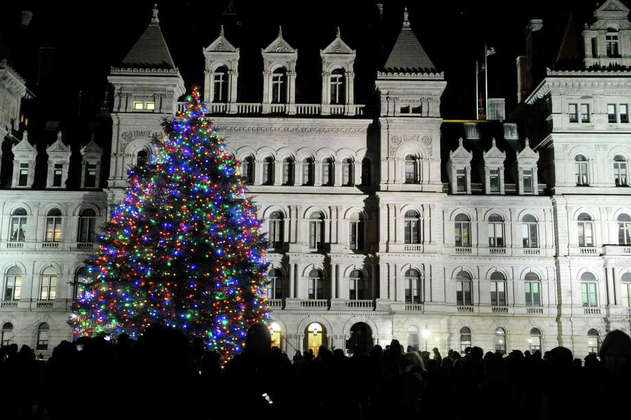 People gather around the holiday tree outside the Capitol  during the tree lighting ceremony for the New York State tree at the Empire State Plaza on Sunday, Dec. 7, 2014, in Albany, N.Y.  (Paul Buckowski / Times Union) Photo: Paul Buckowski / 00029758A