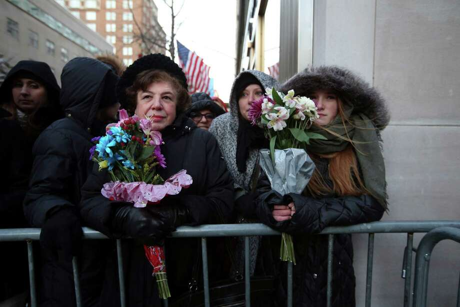 Bystanders hold flowers outside the Carlyle Hotel before the arrival of Prince William and his wife, Kate, in New York, Dec. 7, 2014. After weeks of planning and jitters about protocol, the city welcomed the Duke and Duchess of Cambridge on Sunday for a three-day visit. (Hiroko Masuike/The New York Times) ORG XMIT: XNYT44 Photo: HIROKO MASUIKE / NYTNS