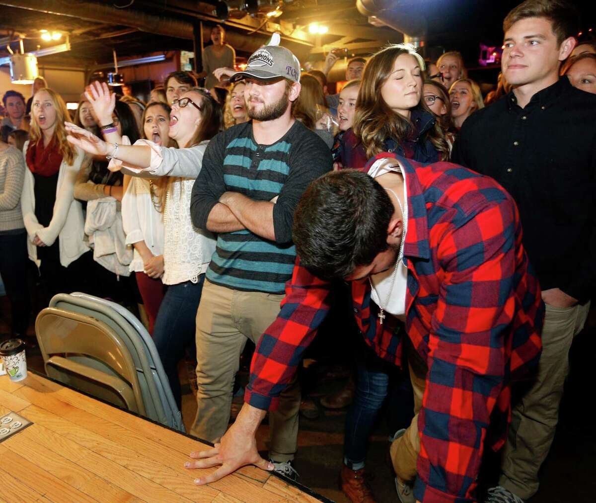 TCU students react, including TCU football player Colten Christensen (wearing hat) and Chase Distasio, foreground with head down, after learning that TCU will not be one of the four teams in the NCAA College Football Playoff at a watch party at the Aardvark near TCU campus Sunday Dec. 7, 2014. (AP Photo/The Fort Worth Star-Telegram, Richard W. Rodriguez) MAGS OUT (FORT WORTH WEEKLY, 360 WEST); ORG XMIT: TXFOR203