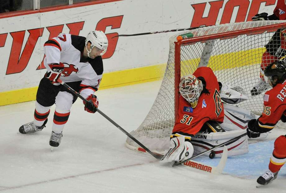 Scott Timmins, left, of the Albany Devils comes around the goal but his shot is stopped in their game against the Adirondack Flames at the Times Union Center on Sunday, Dec. 7, 2014, in Albany, N.Y.  (Paul Buckowski / Times Union) Photo: Paul Buckowski / 00029286G
