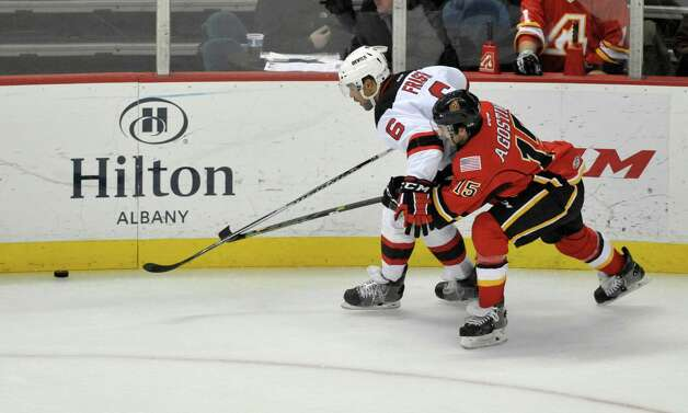 Mark Fraser, left, of the Albany Devils brings the puck up the ice as Ken Agostino of the Adirondack Flames tries to knock the puck away during their game at the Times Union Center on Sunday, Dec. 7, 2014, in Albany, N.Y.  (Paul Buckowski / Times Union) Photo: Paul Buckowski / 00029286G