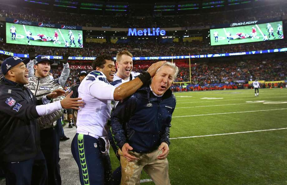 February 2 Seattle Seahawks quarterback Russell Wilson celebrates with coach Pete Carroll after Carroll had Gatorade dumped on his head in the final minutes during Super Bowl XLVIII at MetLife Stadium in New Jersey. The Seahawks dominated the Denver Broncos 42-8. Photo: JOSHUA TRUJILLO, SEATTLEPI.COM / SEATTLEPI.COM
