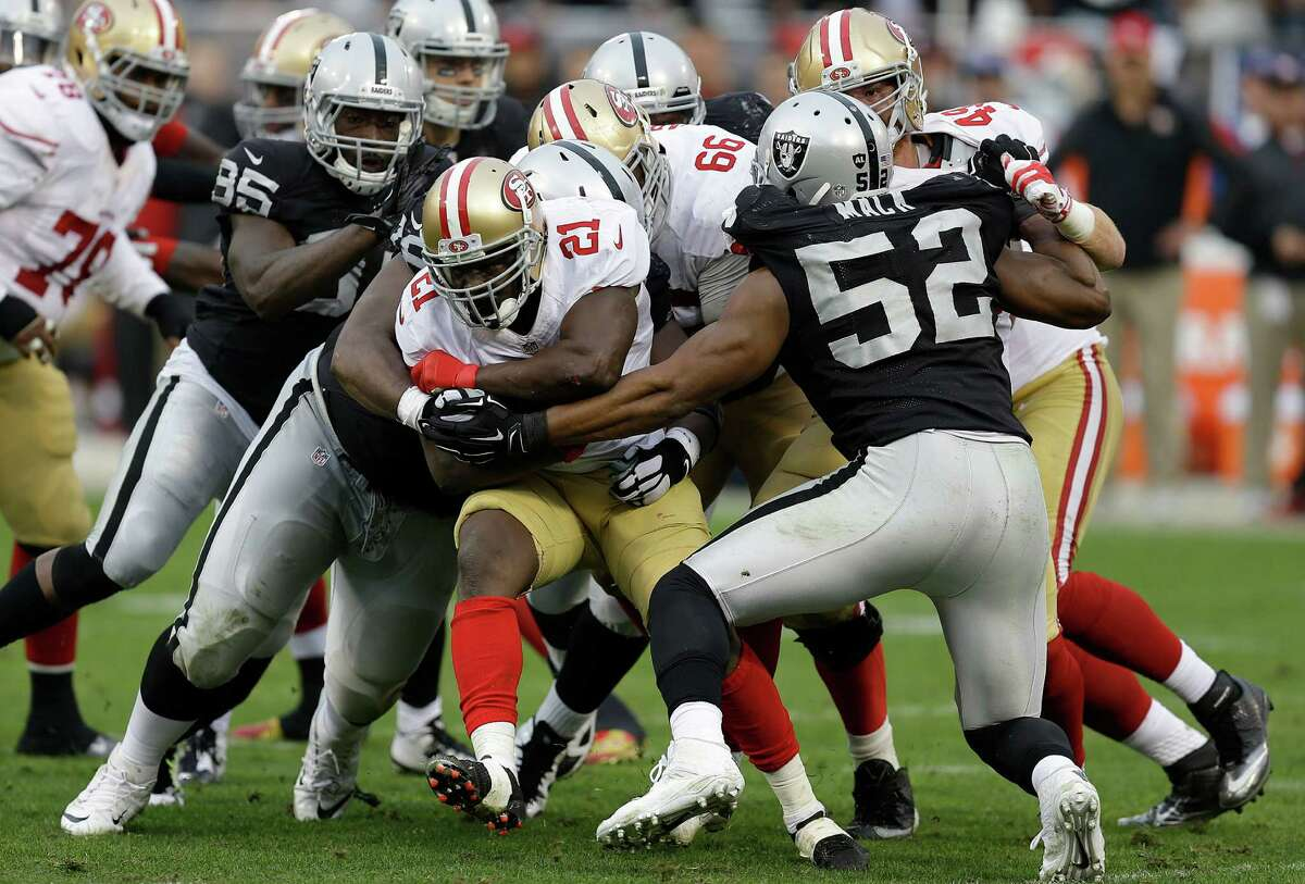 San Francisco 49ers running back Frank Gore (21) is tackled by Oakland Raiders defenders during the third quarter of an NFL football game in Oakland, Calif., Sunday, Dec. 7, 2014. (AP Photo/Ben Margot)