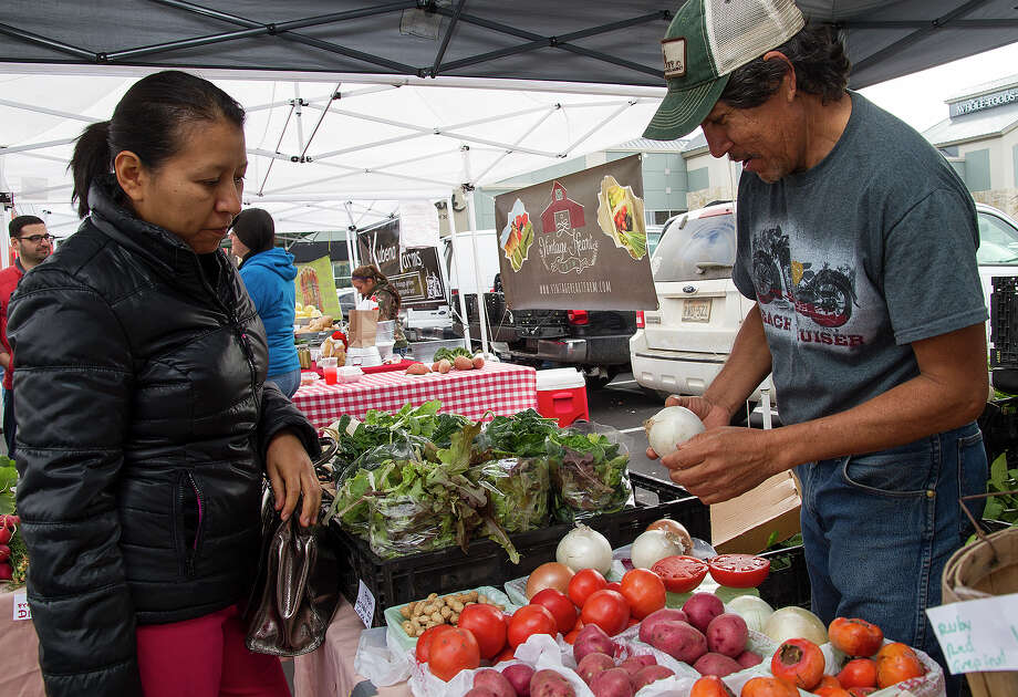 (Left to right) Sandra Martinez with Horacio Zamudio of Zamudio Farms at the Quarry Farmers Market, Sunday, Dec. 7, 2014. This is the market's last day at The Quarry, it's moving to The Yard at 5300 McCullough next week. Photo: Alma E. Hernandez, For The San Antonio Express News / Alma E. Hernandez / For The San