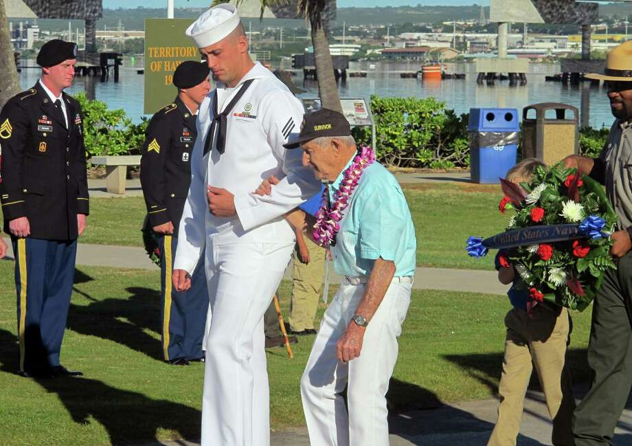 A Navy sailor escorts Navy veteran and Pearl Harbor survivor John Chapman during a ceremony to mark the 73rd anniversary of the Japanese attack on Pearl Harbor, Sunday, Dec. 7, 2014, at Pearl Harbor, Hawaii. The attack launched the U.S. into World War II. (AP Photo/Jennifer Sinco Kelleher) ORG XMIT: RPJSK104 Photo: Jennifer Sinco Kelleher / AP