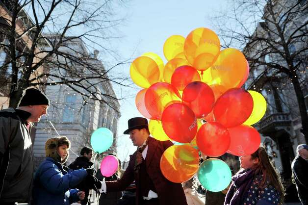 Matthew Harrington, Pioneer Bank senior H.R. generalist,  dresses in period clothing, hands out balloons at the 32nd Annual Troy Victorian Stroll on Sunday, Dec. 7, 2014, in Troy, N.Y.  (Paul Buckowski / Times Union) Photo: Paul Buckowski / 00029717A