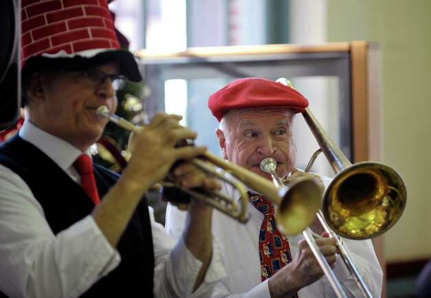 Members of Reggie'ss Red Hot Feetwarmers, Sean Lowery, left, from Scotia, and Tom Shields from Troy perform with the other bank members inside First Niagara bank at  the 32nd Annual Troy Victorian Stroll on Sunday, Dec. 7, 2014, in Troy, N.Y.  (Paul Buckowski / Times Union) Photo: Paul Buckowski / 00029717A