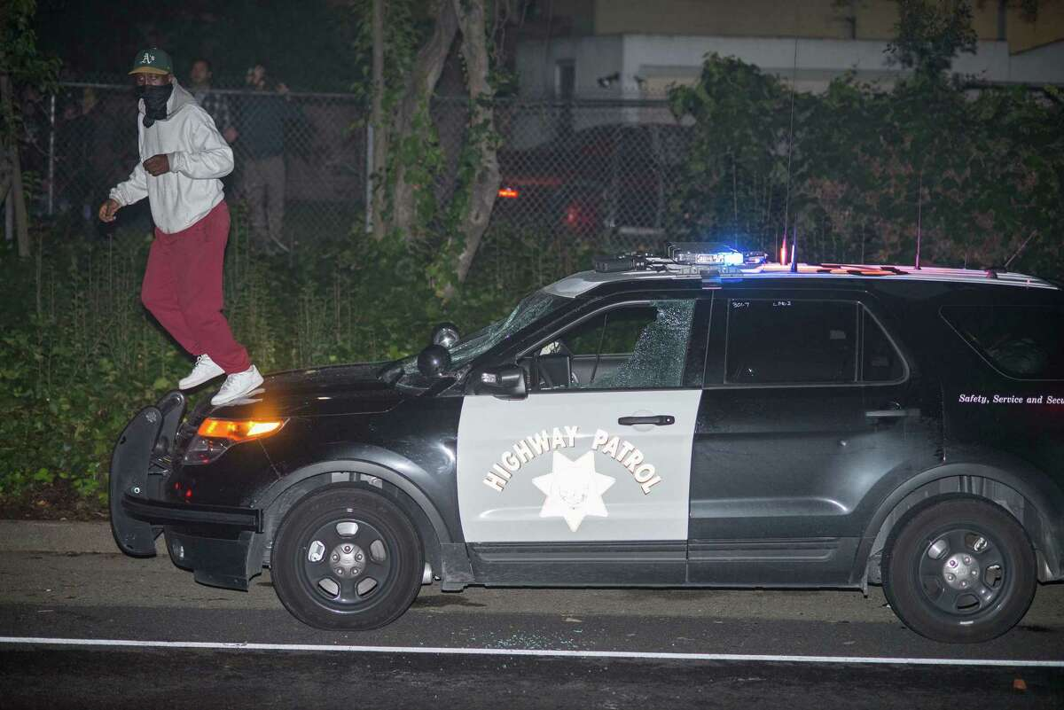 A protester jumps off the hood of one of two damaged California Highway Patrol vehicles after he smashed its windshield on an off-ramp of Highway 24 in Oakland.