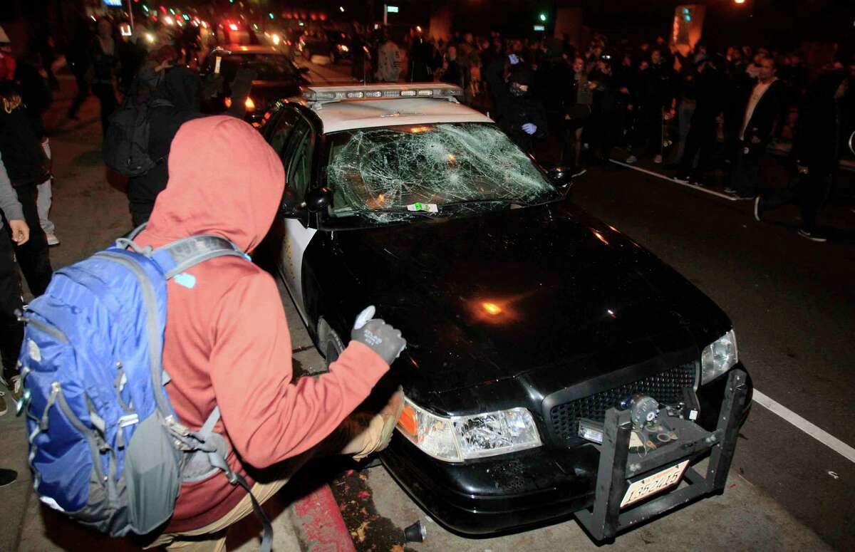 A demonstrator kicks a police car during a protest in Berkeley, Calif. Sunday, December 7, 2014 shining light on the chokehold death of Eric Garner in New York City and the shooting of Mike Brown in Ferguson, Missouri.