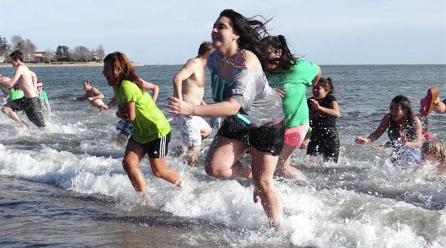 Swimmers race from cold Long Island Sound at Jennings Beach after a brief plunge Sunday to raise money for the Wakeman Boys & Girls Club. Photo: Mike Lauterborn / Fairfield Citizen