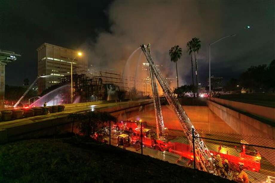 Los Angeles County firefighters battle a fire at an apartment building under construction next to the Harbor CA-110 Freeway in Los Angeles, early Monday, Dec. 8, 2014. The building was not occupied, the Los Angeles Fire Department reported. Photo: Damian Dovarganes, AP Photo/Damian Dovarganes / AP