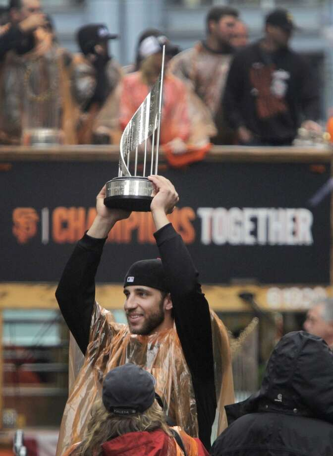 Madison Bumgarner hoists one of his postseason MVP trophies during the Giants' World Series victory parade in San Francisco, Calif. on Friday, Oct. 31, 2014. The Giants captured their third championship in five years after defeating the Kansas City Royals in a seven-game series. Photo: Paul Chinn, The Chronicle