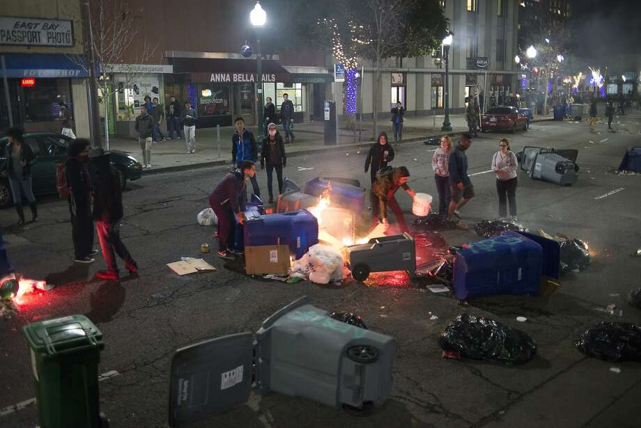 Protestors try to put out fires set by vandals during a demonstration in Downtown Berkeley on December 7, 2014 in Berkeley, Calif. The protesters were demonstrating against recent killings by police. Photo: Sean Havey, The Chronicle