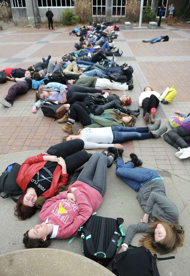 "Greenwich High School seniors Dani Putrino, bottom left, Emma Stow, bottom center, and Charlotte Crouchley lie in the courtyard with others during the Can't Breathe ""Die-In"" at Greenwich High School in Greenwich, Conn. Monday, Dec. 8, 2014.  More than 100 students lay in the school courtyard in silence to make a statement against the unequal treatment of minorities by local and national police departments.  The protest stems from grand jury decisions not to indict Ferguson and Staten Island police officers in the killings of Michael Brown and Eric Garner. Photo: Tyler Sizemore / Greenwich Time"