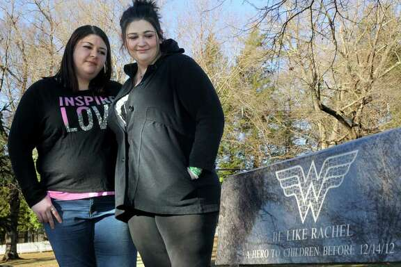 Sarah D'Avino, 27, left and Hannah D'Avino, 24, are the sisters of Sandy Hook Elementary School victim, Rachel D'Avino. The sisters are photographed with a bench dedicated to Rachel on the town green in Bethlehem, Conn., their home town, Sunday, Dec. 7, 2014.