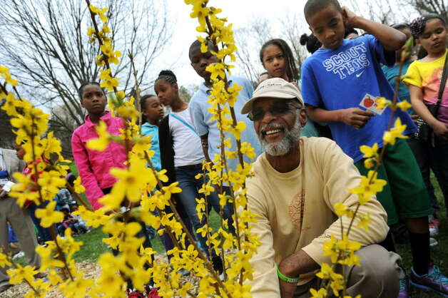 Yusuf Burgess of Ed-Venture and Nature Network, center, is seen helping to plant forsythia in a new schoolyard garden on Tuesday, April 22, 2014, at Arbor Hill Elementary in Albany, N.Y. (Cindy Schultz / Times Union)   Cindy Schultz