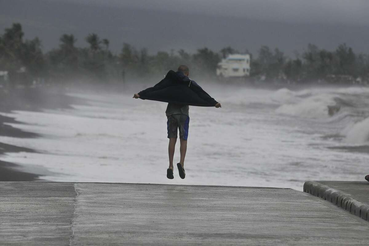 AND HE WAS NEVER SEEN AGAIN: A Filipino man tries to catch the typhoon-force winds with his jacket in Legazpi, Philippines. Typhoon Hagupit knocked out power in entire coastal provinces and mowed down trees, but it weakened quickly Sunday, sparing the Philippines a repeat of the unprecedented devastation from last year's monster storm.