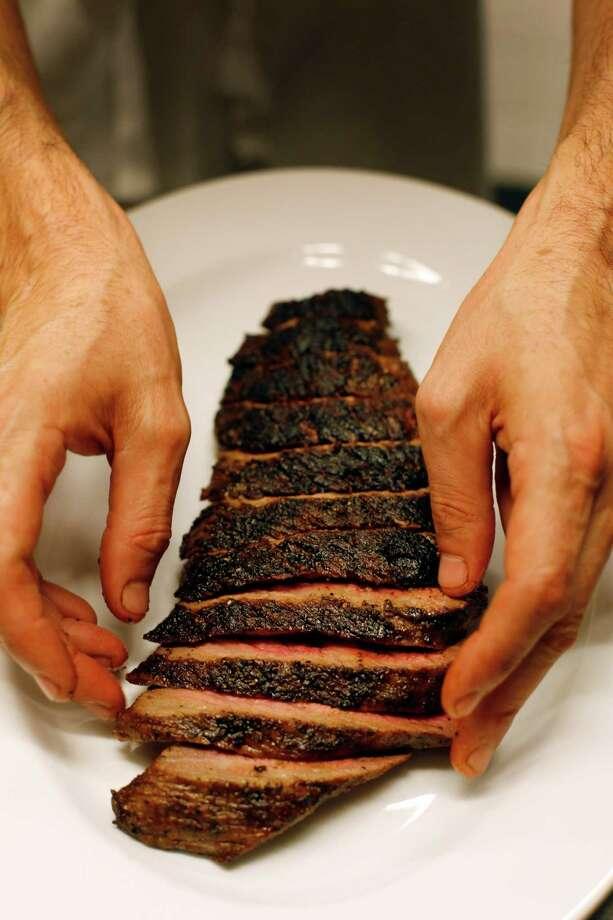 Executive Chef Trevor Kunk plates a tri-tip steak at Press restaurant. Photo: Pete Kiehart / The Chronicle / ONLINE_YES