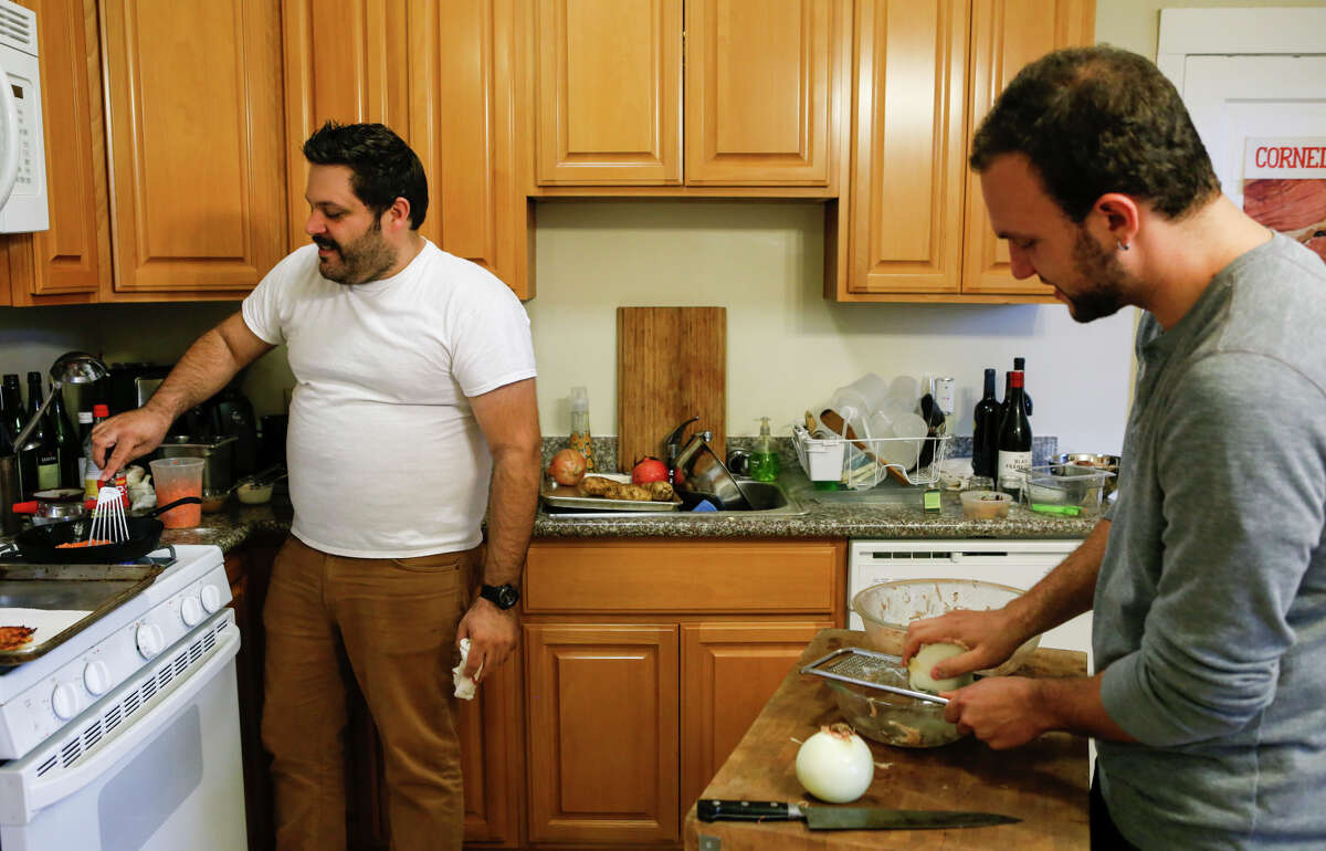 Evan Bloom (left) and Leo Beckerman of Wise Sons Jewish Delicatessen make latkes in prepration for Haunkkah.