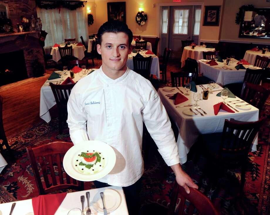 Chef Granit Balidemaj, a Greenwich resident, with a plate of Caprese (tomatoes, green basil, mozzarella and extra-virgin olive oil) he prepared at Alba's Restaurant where he works in Port Chester, N.Y., Wednesday, Dec. 3, 2014. Balidemaj has started Granit Events & Catering, a full service event and catering company that is located in Greenwich. Photo: Bob Luckey / Greenwich Time