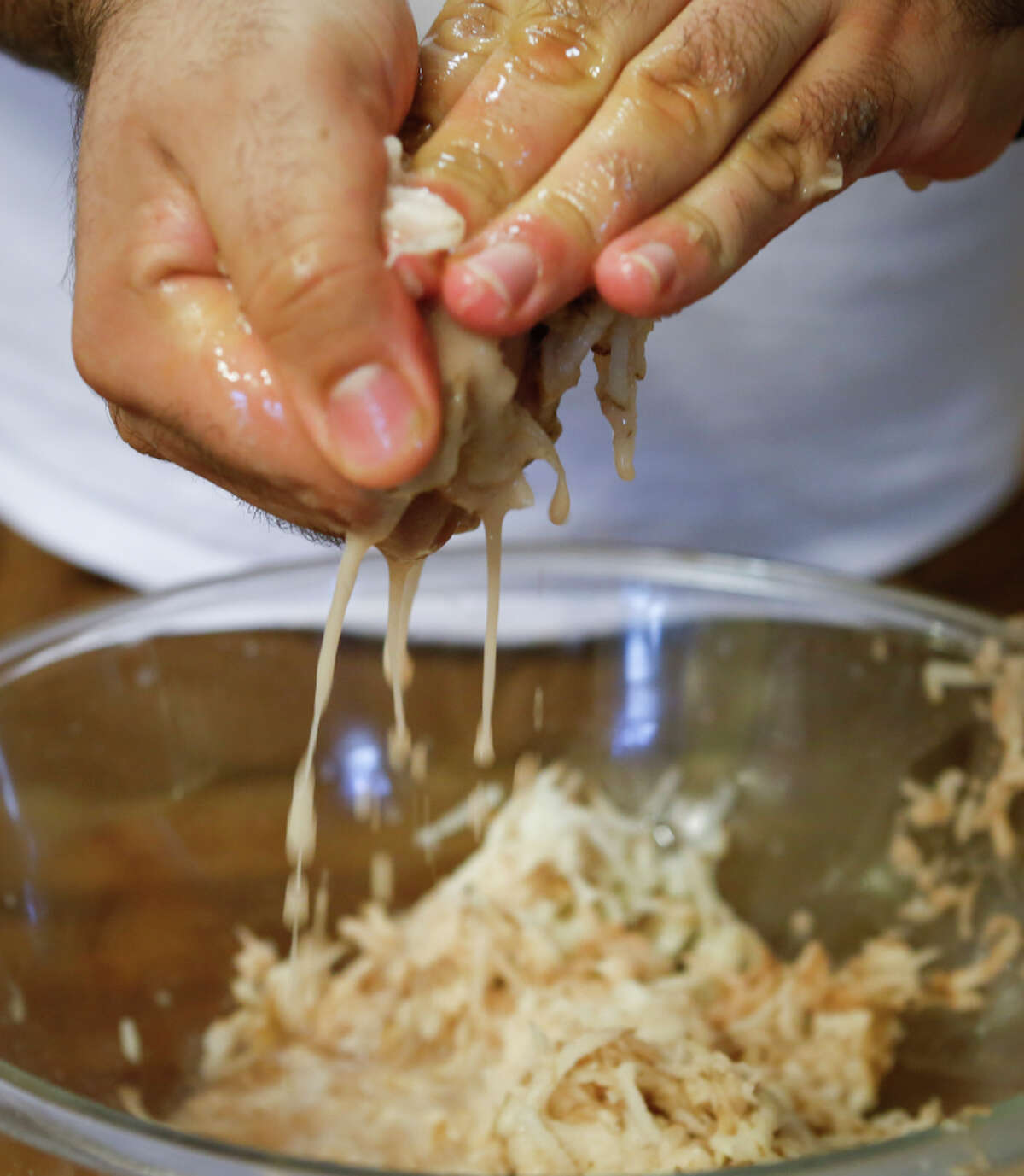 Squeezing the excess moisture from the grated potatoes also ensures the latkes will be crunchy instead of soggy.