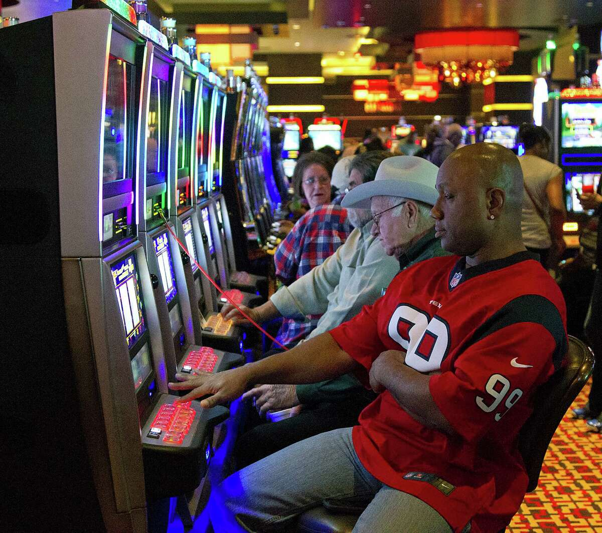Charles Butcher right, of Houston plays a slot machine at the Golden Nugget Hotel & Casino Monday, Dec. 8, 2014, in Lake Charles.