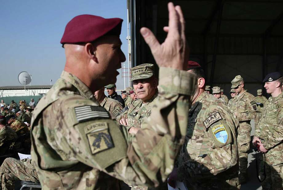 Gen. John Campbell, commander of NATO's International Security Assistance Force, takes part in a flag-lowering ceremony in Kabul International Airport in Afghanistan.Commander of International Security Assistance Force, General John F. Campbell, center, takes part in a flag-lowering ceremony in Kabul International Airport in Kabul, Afghanistan, Monday, Dec. 8, 2014. The U.S. and NATO ceremonially ended their combat mission in Afghanistan on Monday, 13 years after the Sept. 11 terror attacks sparked their invasion of the country to topple the Taliban-led government. (AP Photo/Massoud Hossaini) Photo: Massoud Hossaini / Massoud Hossaini/Associated Press / AP