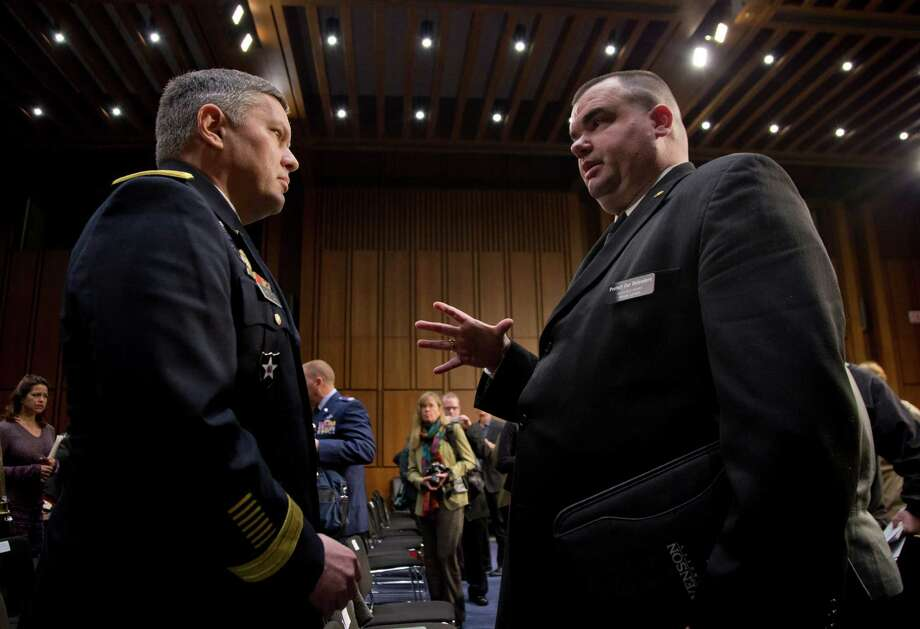 Maj. Gen. Gary Patton (left) of the Pentagon's sexual assault prevention office speaks with Brian Lewis, an ex-sailor who told U.S. senators he was raped by a higher-ranking sailor.Maj. Gen. Gary Patton, director of the Sexual Assault Prevention and Response Office, left, speaks with Brian Lewis ?former Petty Officer Third Class, U.S. Navy, right, on Capitol Hill in Washington, Wednesday, March 13, 2013, after Lewis testified before the Senate subcommittee on Personnel hearing on sexual assault in the military. Brian Lewis, a former Navy petty officer, told the subcommittee not to forget that many victims of sexual assault and harassment in the military are male. Lewis said he was raped in 2000 by a non-commissioned officer who outranked him. His commanders ordered him not to report the crime to Naval Criminal Investigative Service. Lewis said he was later misdiagnosed with having a personality disorder and he was discharged from the service in 2001. (AP Photo/Carolyn Kaster) Photo: Carolyn Kaster / Associated Press File Photo / AP