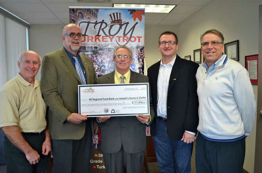 The Regional Food Bank of Northeastern New York and Joseph's House & Shelter received a combined $11,498 raised by participants in the 67th Troy Turkey Trot on Thanksgiving. From left are Mark Quandt, food bank executive director; Kevin O'Connor, executive director of Joseph's House, Troy Mayor Lou Rosamilia; Anthony Bruno, CEO of SportsSignUp; and George Regan, Turkey Trot director.   (Photo by Edward Parham)