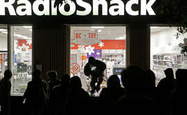 A looter leaps out of a Radio Shack on Shattuck Avenue in Berkeley after protests against police killings of unarmed black men in Missouri and New York spiraled into vandalism.